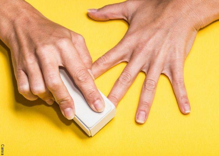 Foto de una mujer polichando sus uñas para la manicura japonesa restaura la uña