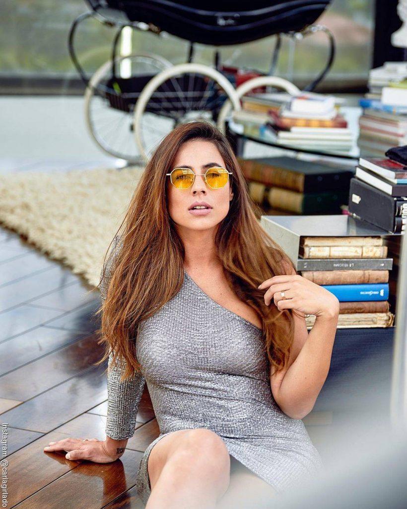 Foto de Carla Giraldo con un vestido gris, sentada y gafas de color amarillo