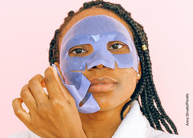 Foto de una mujer retirándose una mascarilla del rostro