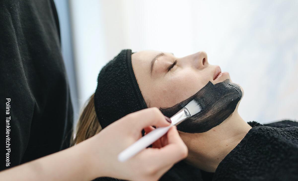 Foto de una mujer aplicando una mascarilla negra a otra