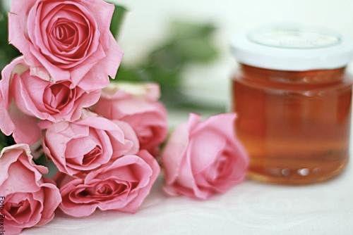 Foto de un frasco de miel y varias rosas
