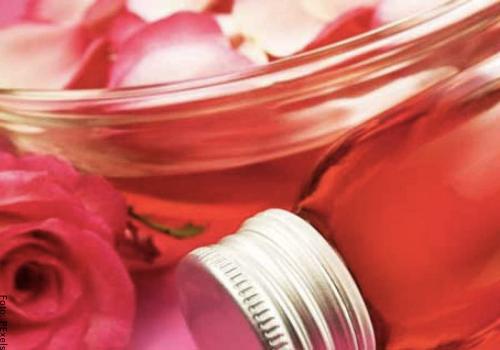 Foto de una rosa y un frasco para ilustrar para qué sirve la miel de rosas
