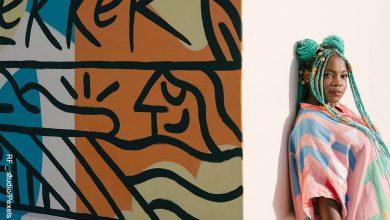 Foto de una mujer frente a un mural que ilustra los peinados con trenzas africanas