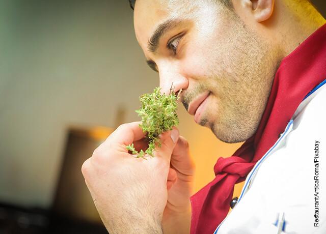 Foto de un chef oliendo una rama de especias