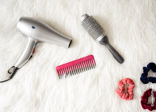Foto d una secadora y varios cepillos de pelo sobre una cobija de peluche