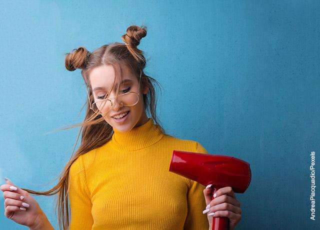 Foto de una mujer sosteniendo una secador de pelo rojo