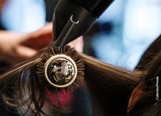 Foto de un mechón de pelo con un cepillo y un secador