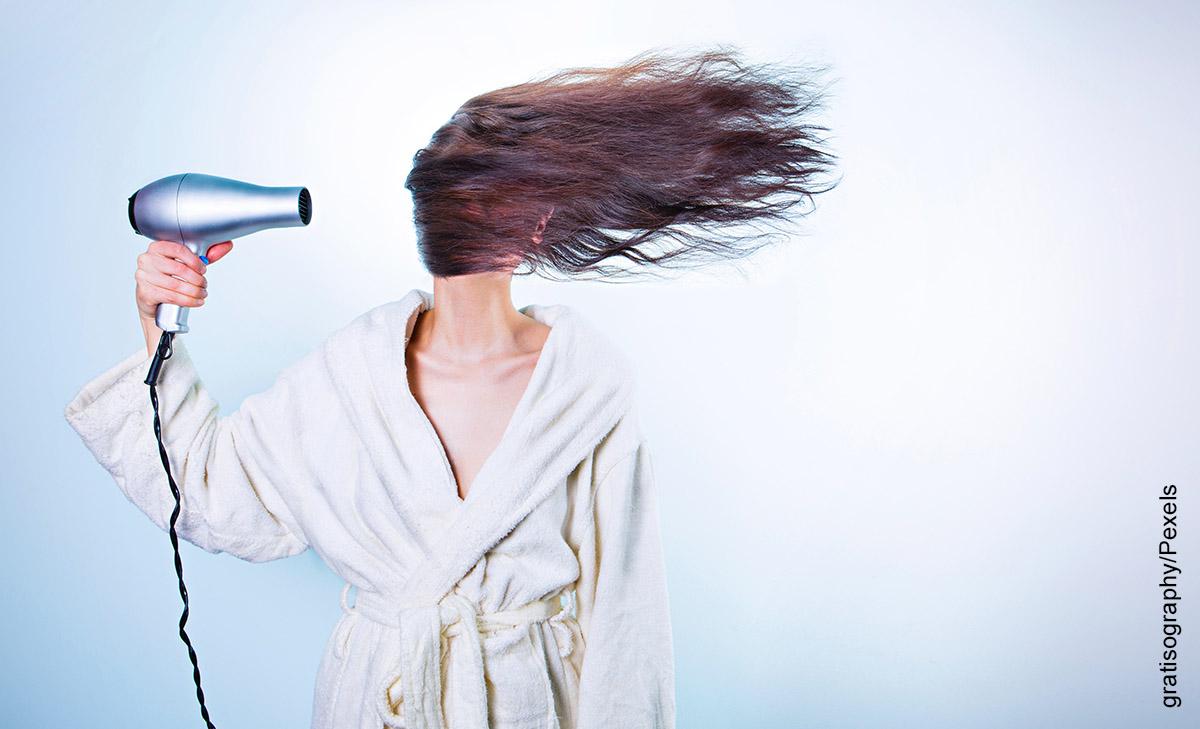 Foto de una mujer usando una secadora de cabello mientras se despeina