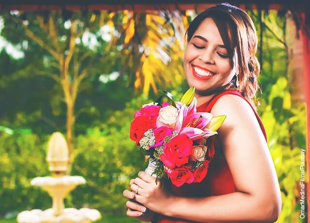 Foto de una mujer sonriente con un ramo de flores