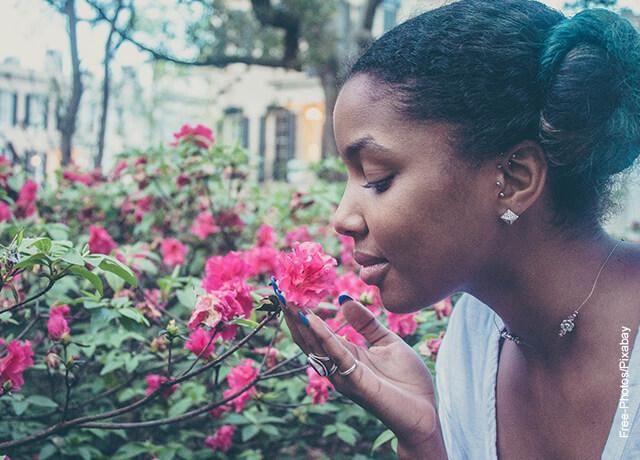Foto de una mujer oliendo unas flores fucsias en la calle