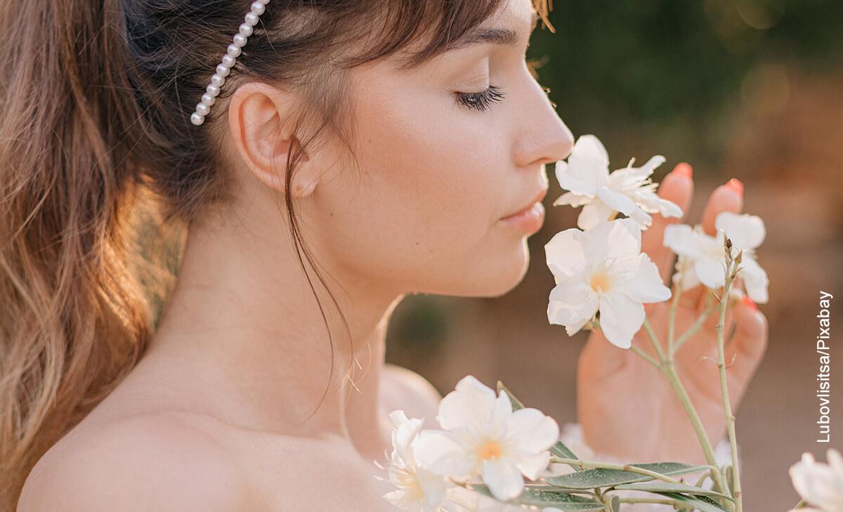 Foto de una mujer oliendo margaritas en el campo que ilustra el significado de las flores