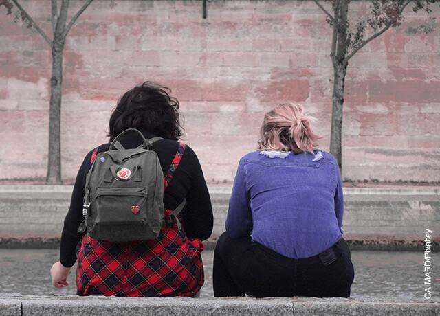 Foto de dos mujeres sentadas en un andén distanciadas