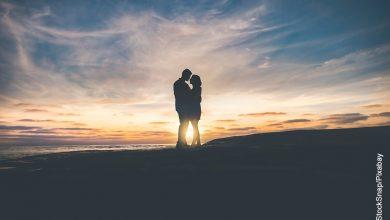 Foto de una pareja besándose al atardecer que ilustra los signos compatibles con Leo