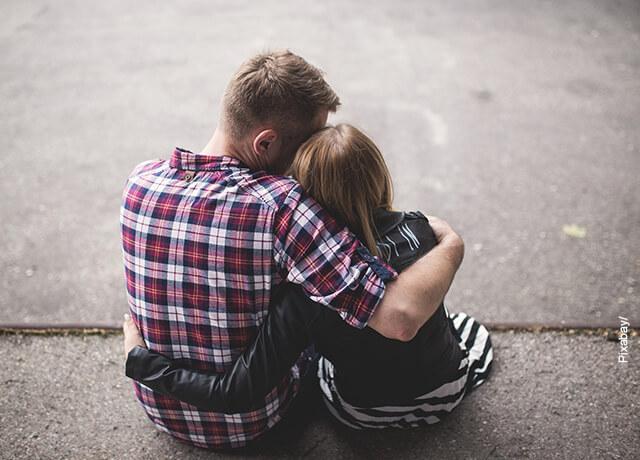 Foto de una pareja abrazada y sentada en un andén que ilustra los signos compatibles con Virgo