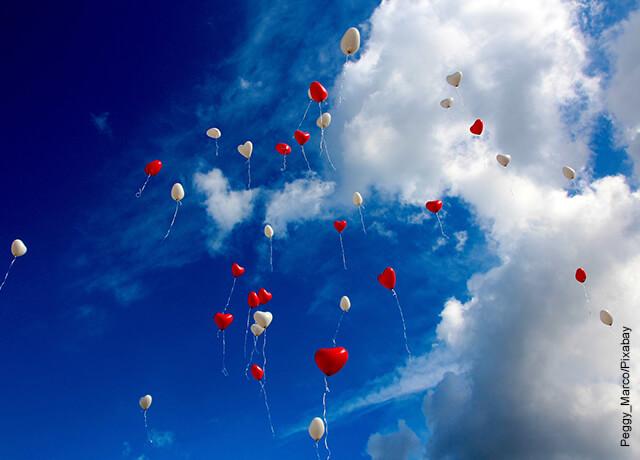 Foto de globos rojos y blancos yendo hacia el cielo