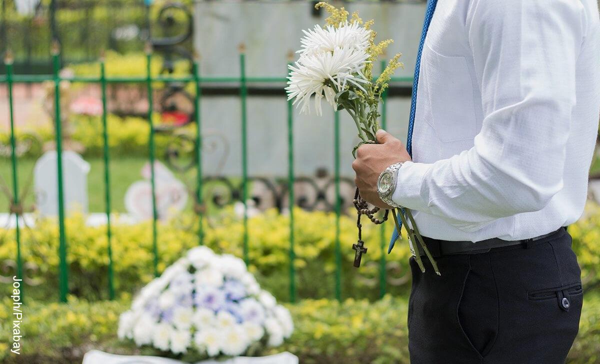 Foto de un hombre en un cementerio con flores que ilustra soñar con un velorio