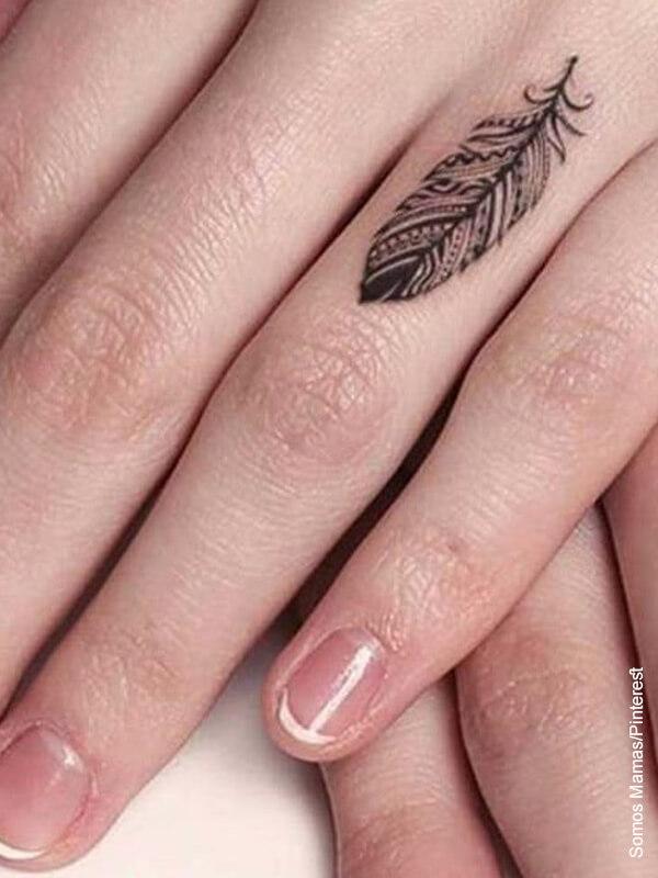 Foto de la mano e una mujer que luce sus tatuajes en los dedos de plantas