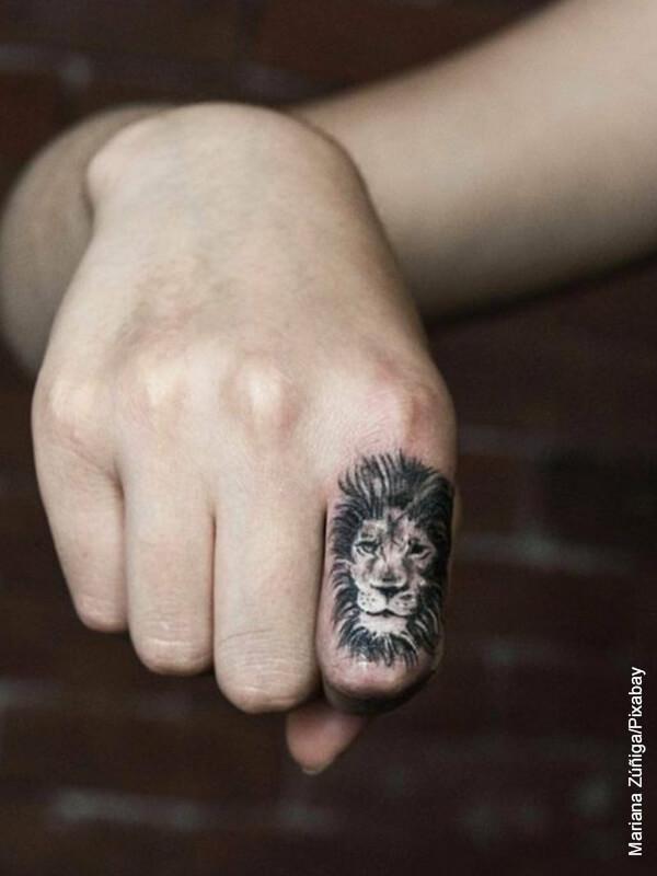 Foto de la mano de un hombre con un tatuaje de león