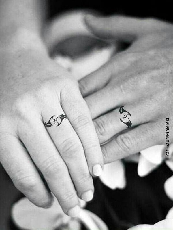 Foto de una pareja que muestran tatuajes de anillo de bodas en sus manos