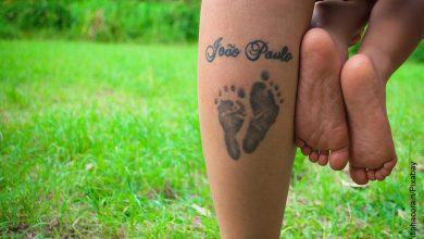 Foto de una mujer con un tatuaje en su pie, cargan a su bebé que ilustra los tatuajes para hijos
