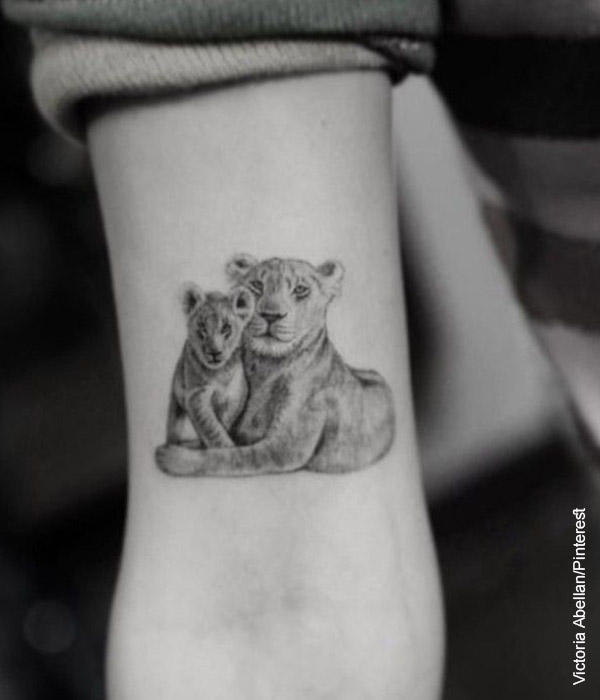 Foto de un brazo tatuado con una leona y su cría