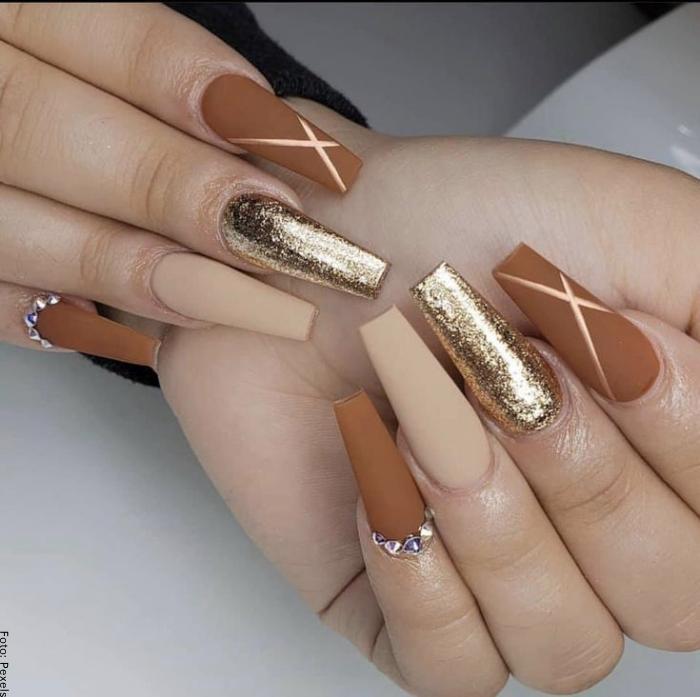 Foto de uñas acrílicas en tonos dorados y brillantes