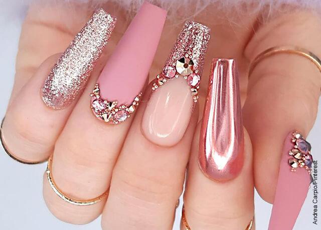Foto de las uñas de una mujer con apliques y pedrería metalizada