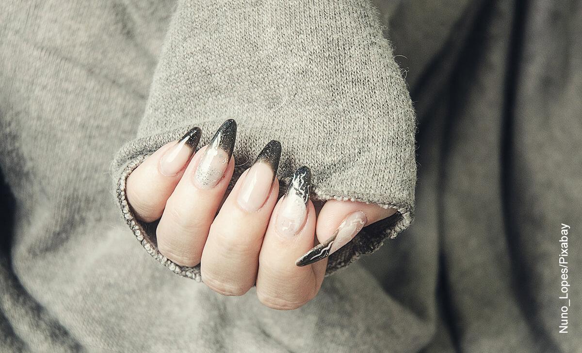 Foto de la mano de una mujer que muestra las úñas en resina