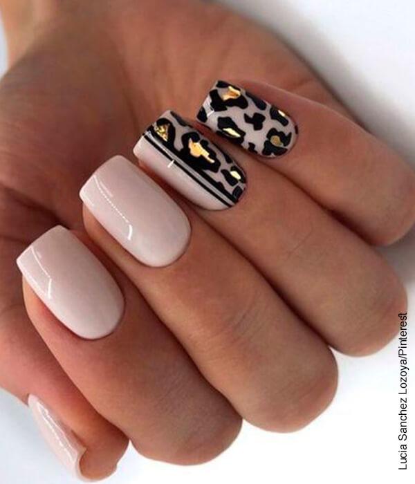 Foto de la mano de una mujer con un manicure de animal print