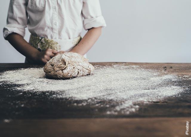 Foto de una bola de masa para pan sobre una mesa de madera