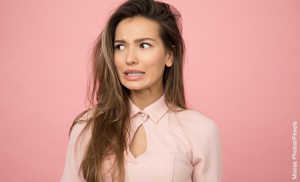 Foto de una mujer con cara preocupada que ilustra la caída del cabello