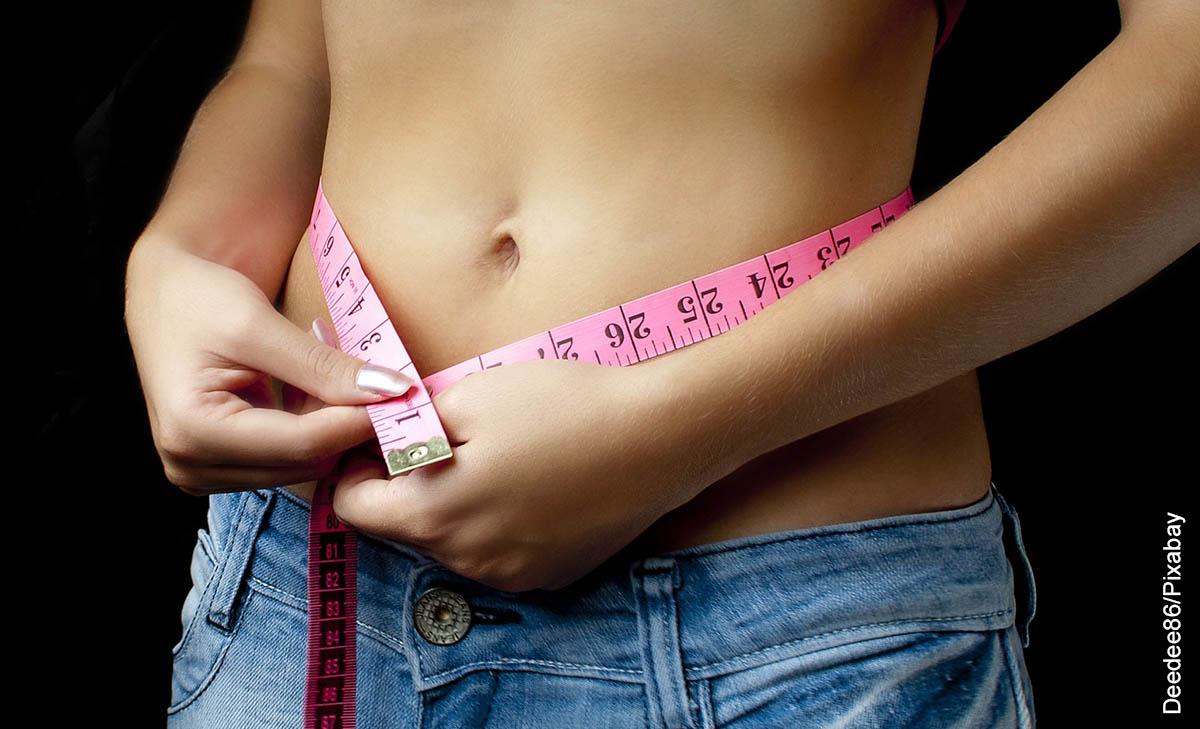 Foto de una mujer midiendo su cintura que muestra cómo reducir el abdomen