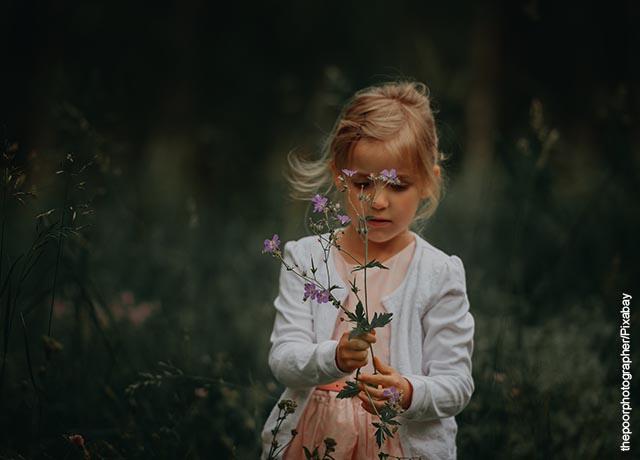 Foto de una niña con unas flores violetas en sus manos