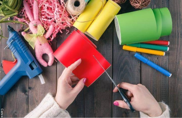 Foto de manos de mujer recortando papel rojo