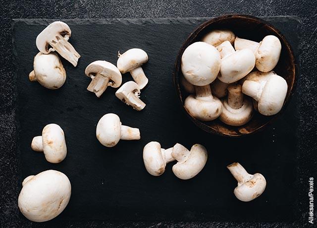 Foto de champiñones enteros y cortados