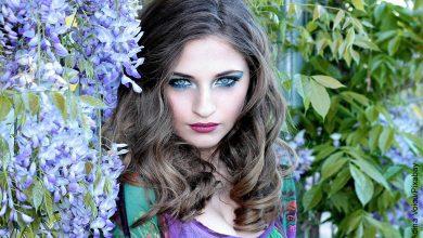 Foto de una mujer de ojos claro posando junto con muchas flores que muestra el maquillaje para ojos