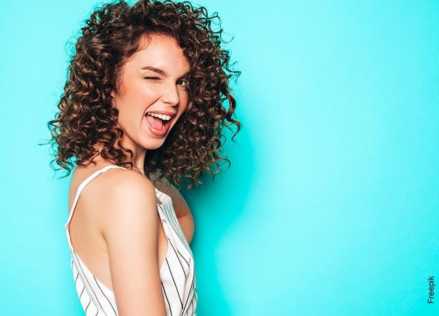 Foto de una mujer sonriendo y picando el ojo a la cámara que muestras las mascarillas para cabello seco