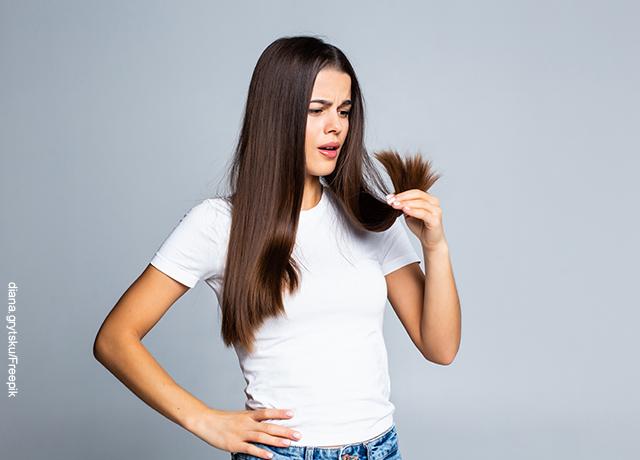 Foto de una joven mirando preocupada las puntas del pelo