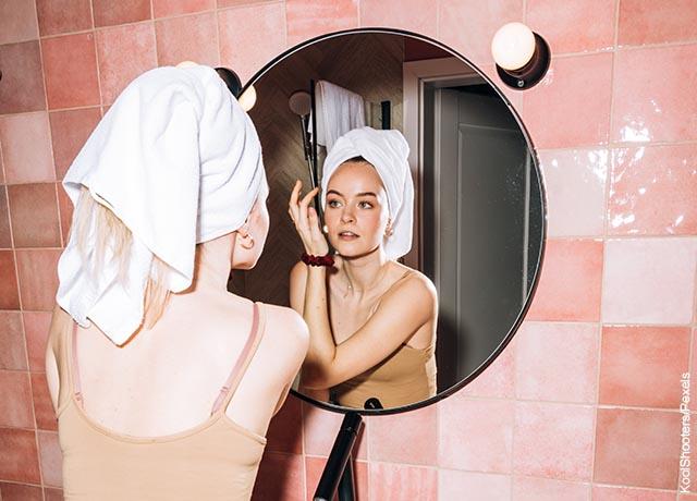 Foto de una mujer retocando su maquillaje frente al espejo