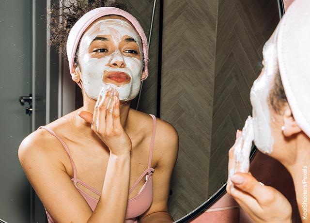 Foto de una mujer aplicando una crema blanca en su cara