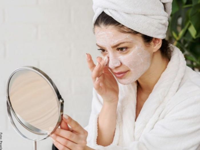 Foto de una mujer con mascarilla frente al espejo