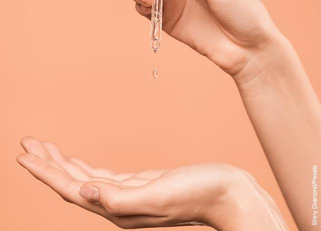 Foto de una mujer aplicando aceite en sus manos que muestra las mascarillas para el cabello