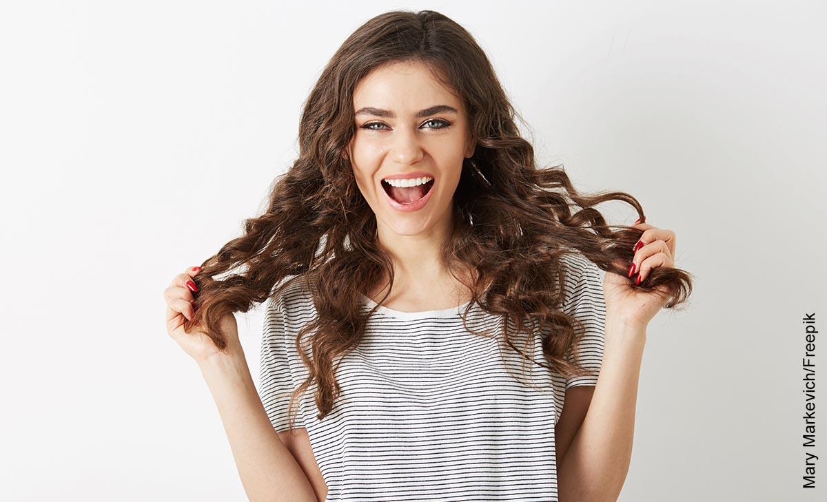 Foto de una mujer tomando su pelo rizado mientras sonríe