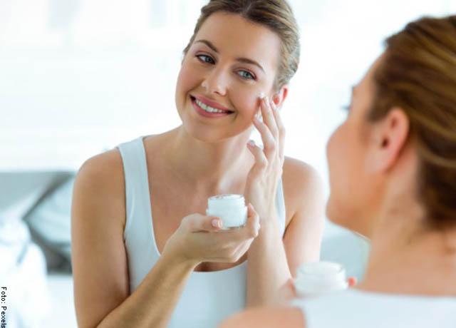 Foto de una mujer aplicando una crema en su rostro