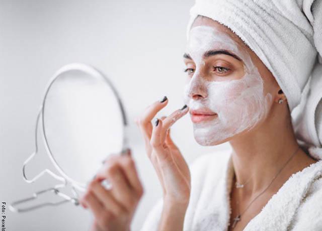 Foto de una mujer mirándose al espejo mientras se aplica una crema en la cara