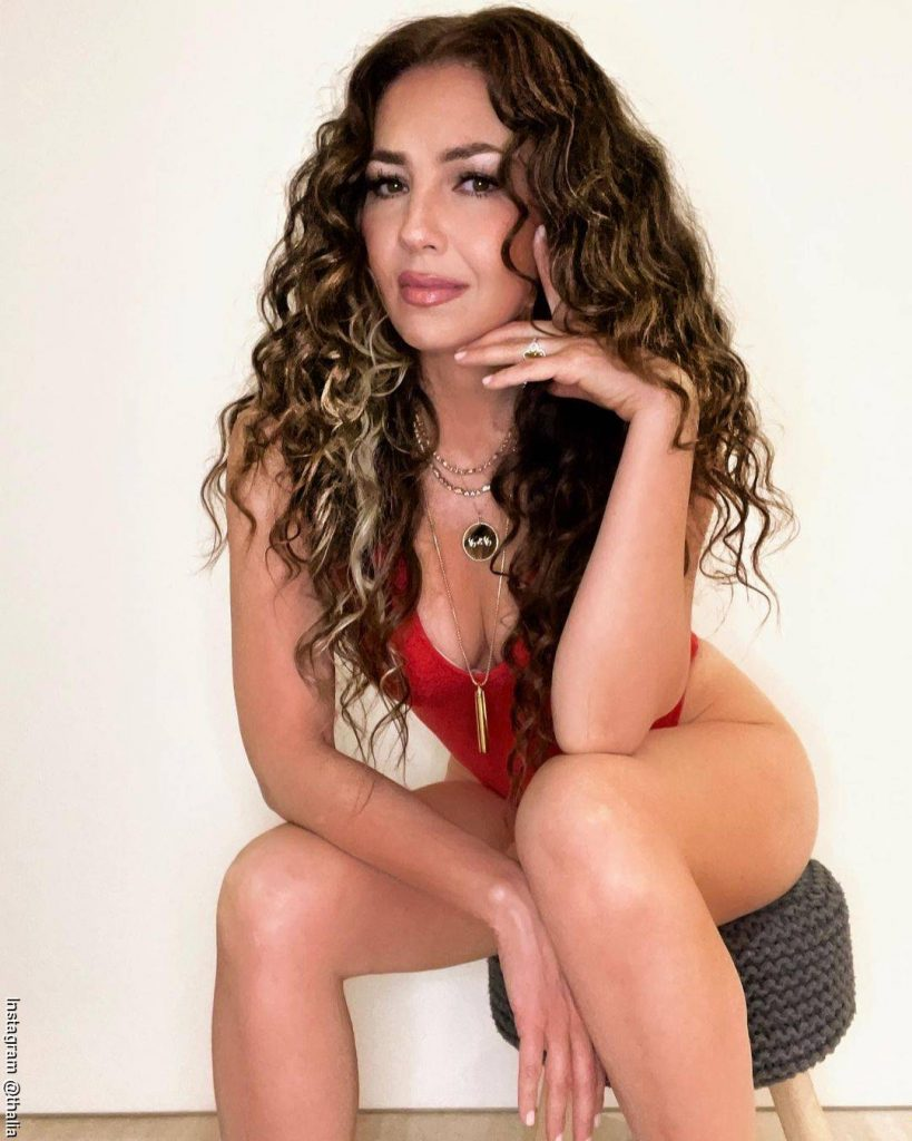 Foto de Thalía sentada de frente con un traje de baño rojo