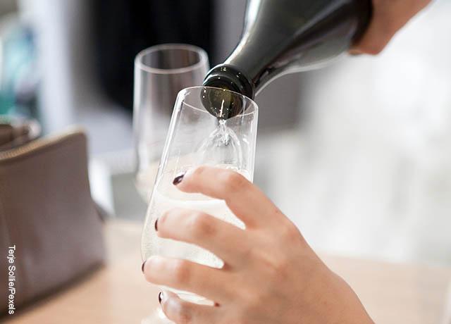 Foto de una mujer sirviendo una copa de champaña