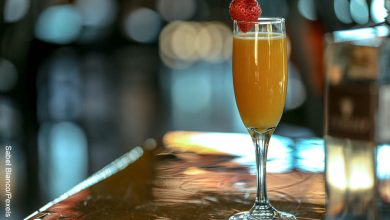 Foto de una copa con una bebida de naranja que muestra cómo hacer mimosa con su receta clásica