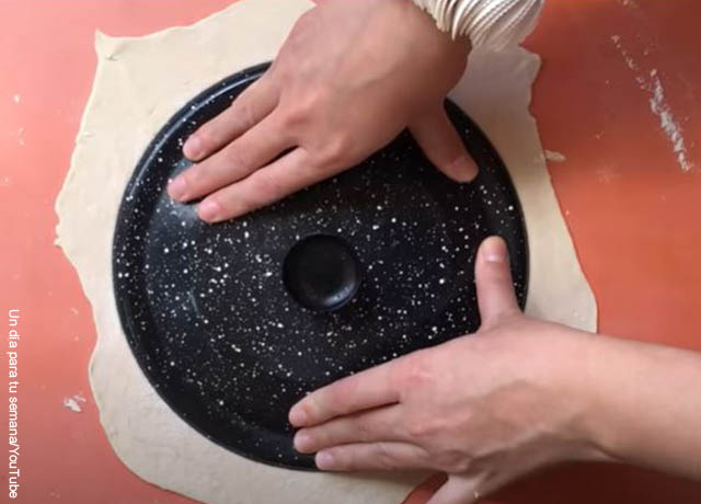 Foto de unas manos cortando una masa con una tapa de olla