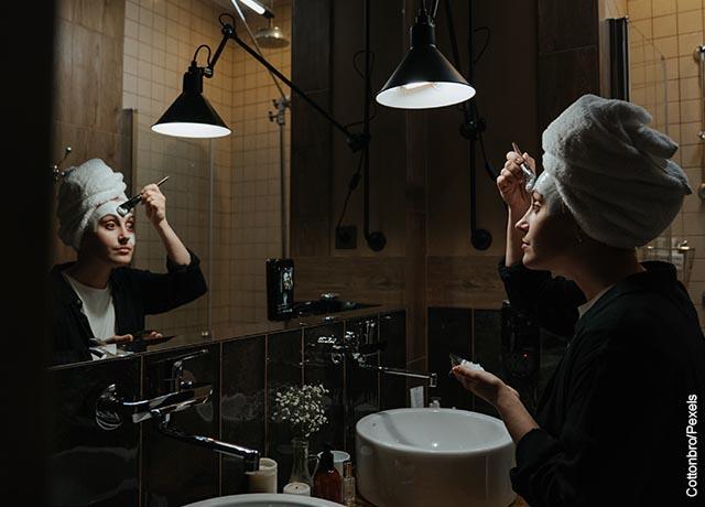 Foto de una mujer aplicando una crema en su cara con una brocha